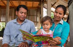 Sopheak and her husband, Mr Chruy Mann (left), reading a book with their daughter, Mann Sophary (middle).